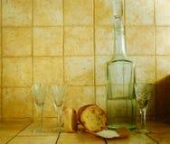 Líquido em um frasco, em uns wineglasses, em um pão e em um sal Imagem de Stock Royalty Free