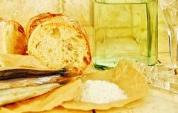 Líquido em um frasco, em uns wineglasses, em um pão e em um sal Fotos de Stock