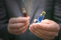 Líquido esencial de la píldora azul y roja en manos del hombre de negocios Opción correcta de medicamentos Fotografía de archivo libre de regalías