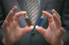 Líquido esencial de la píldora azul y roja en manos del hombre de negocios Opción correcta de medicamentos Foto de archivo