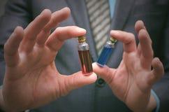 Líquido esencial de la píldora azul y roja en manos del hombre de negocios Opción correcta de medicamentos Imagen de archivo