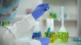 Líquido orgânico do gotejamento do bioquímico da garrafa com a planta no tubo com agente azul video estoque