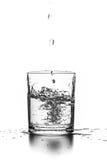 Líquido que vierte en un vidrio Fotografía de archivo