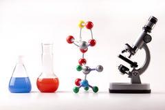 Líquido y átomos de la bruja del microscopio y de los frascos Fotos de archivo