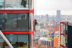 Líquidos de limpeza de janela que trabalham em uma construção alta da elevação imagem de stock royalty free
