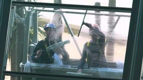 Líquidos de limpeza que lavam janelas da construção alta da elevação, ocupação arriscada, perigo da vida video estoque