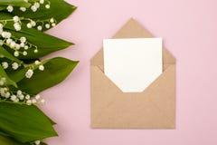 Lírio festivo da flor da composição e do convite do vale no envelope do ofício no fundo do rosa pastel Vista aérea, bouqu foto de stock royalty free