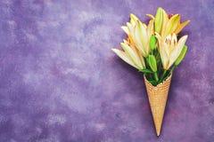 Lírios amarelos em um cone do waffle no fundo roxo abstrato Fundo criativo da mola bonita, lugar para o texto fotografia de stock