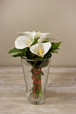 Lírios de calla brancos no vaso no fundo de madeira Fotos de Stock Royalty Free
