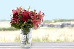 Lírios vermelhos e cor-de-rosa em um vaso de cristal fotografia de stock