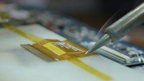 Löda en chip att att löda en microcircuit Löda en bruten datorchip arkivfilmer