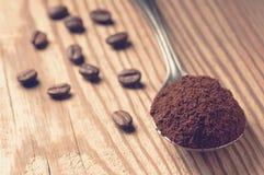 Löffel des gemahlenen Kaffees und der Kaffeebohnen auf hölzernem Brett, flache Schärfentiefe konzentrierte sich auf gemahlenen Ka Stockfoto