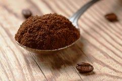 Löffel des gemahlenen Kaffees und der Kaffeebohnen auf Holztisch, niedrige Winkelsicht mit flacher Schärfentiefe Stockfotos