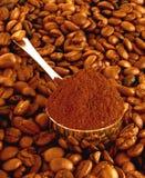 Löffel des Kaffees auf Körnern eines Hintergrundes Stockfotos