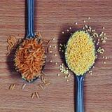 Löffel mit braunem Reis und Hirse stockbilder