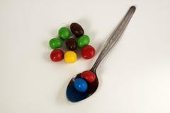 Löffel mit bunten Süßigkeiten Stockfotos
