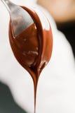 Löffel mit flüssiger Schokolade Stockbild