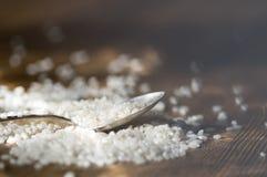 Löffel mit Reis auf Holztisch Lizenzfreie Stockbilder
