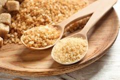 Löffel und brauner Zucker auf Tabelle lizenzfreies stockbild