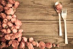 Löffel und Gabel über einem Holztisch mit roten Rosen Stockfotos