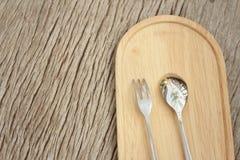 Löffel und Gabel auf einem Hintergrund des braunen Holzes Stockfotos