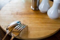 Löffel und Gabel gebunden auf Holztisch Stockfoto