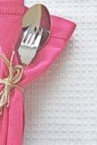 Löffel und Gabel mit rosafarbener Serviette Stockbilder