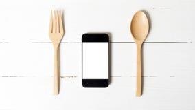 Löffel und intelligentes Telefonkonzept, die soziales essen Lizenzfreies Stockfoto