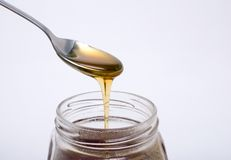 Löffel voll des Honig- und Glasglases lizenzfreies stockbild