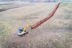 Löffelbaggerbagger, der einen Abzugsgraben gräbt Stockfotos