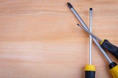 Lögn en för tre skruvmejslar på annan i rätsidan på en träbakgrund Royaltyfria Foton