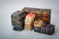 Lögn för gamla böcker bredvid den gamla resväskan Fotografering för Bildbyråer