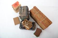 Lögn för gamla böcker bredvid den gamla resväskan Royaltyfria Bilder