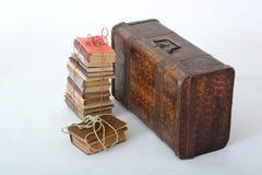 Lögn för gamla böcker bredvid den gamla resväskan Royaltyfri Bild