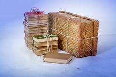 Lögn för gamla böcker bredvid den gamla resväskan Arkivbild