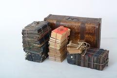 Lögn för gamla böcker bredvid den gamla resväskan Arkivfoto