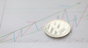 Lögn för Litecoin cryptocurrencymynt på tabellen med arkivbilder