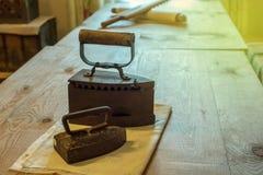 Lögn för strykjärn två på tabelltorkduken, ryska metalljärn för 19th århundrade som används av gammelfarfäder Arkivfoto