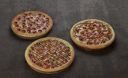Lögn för tre pizza på trätabellen Royaltyfri Foto