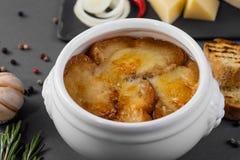 Lök-ost soppa med krutonger i en vit kruka på en grå bakgrund Delishious fransmansoppa Royaltyfria Foton