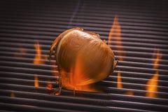 Lök på ett varmt flammande galler Arkivfoto