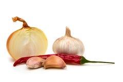 Lök, vitlök, persilja och chilipeppar på vit bakgrund Royaltyfri Foto