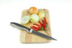 Lökar och chilies på skärbräda Royaltyfri Foto