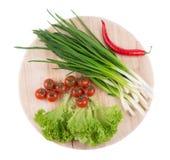 Lökar och körsbärsröda tomater Arkivfoto