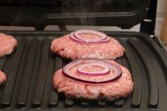 Lökcirklar ligger på ett stycke av kött i gallret Royaltyfria Foton