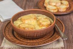 Löksoppa med den rostade bagetten på tabellen som göras av ekplankor Franskt matbegrepp medf8ort arkivfoton