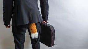 Lömsk affärsman i svart dräkt med en portfölj och en rävsvans royaltyfria foton
