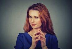 Lömsk, slug beräknande ung kvinna som konspirerar något Royaltyfria Bilder