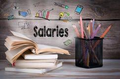 Lön affärsidé Bunt av böcker och blyertspennor på trätabellen royaltyfri foto