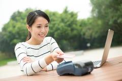 Lön för ung kvinna på pos.-terminalen med kreditkorten Arkivbild